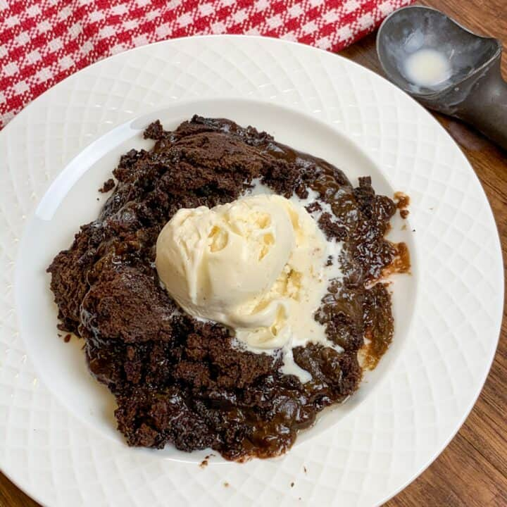 Slow cooker chocolate cake on a plate with vanilla ice cream