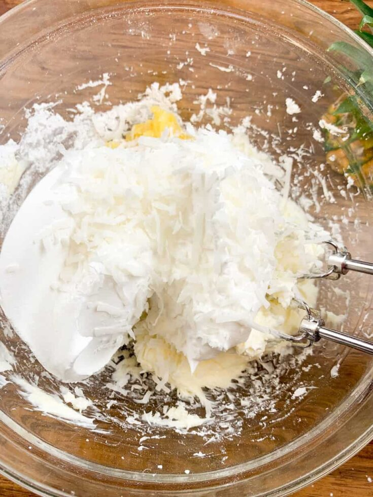 Crushed pineapple, cream cheese, whipped topping, and powdered sugar mixed up in a bowl