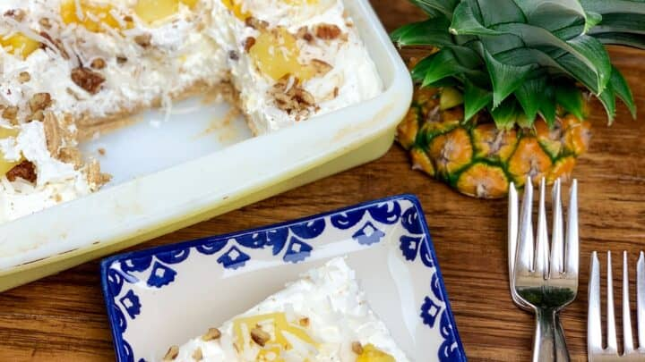Pineapple lush on a blue and white plate with a casserole dish