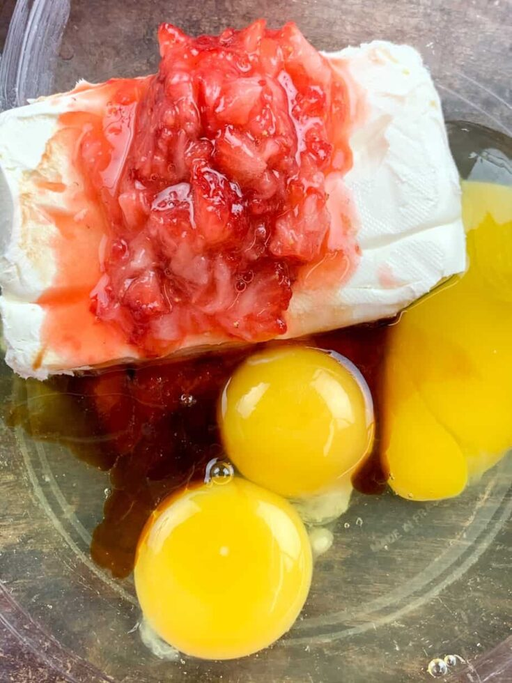 Strawberries, eggs, and cream cheese in a large bowl