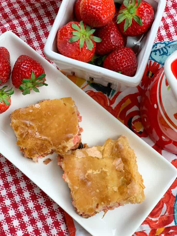 Strawberry chess squares on a plate with strawberries on the side