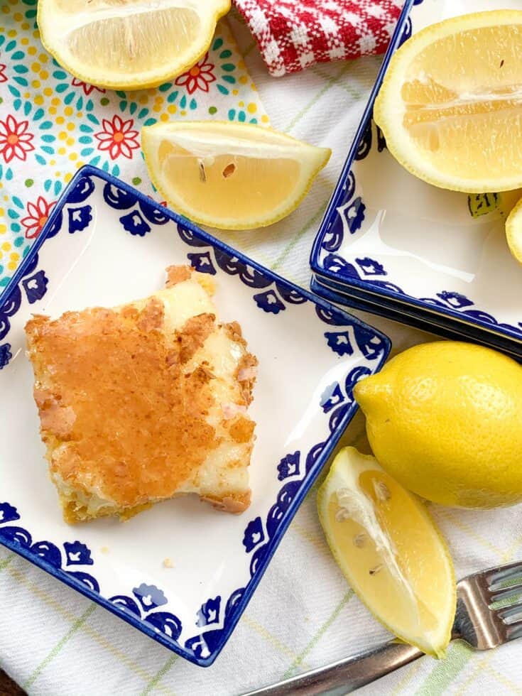 Lemon chess squares on a plate with sliced lemons