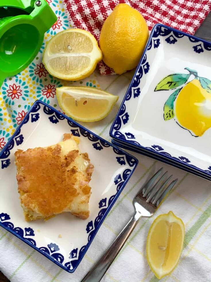 Lemon chess squares on a plate with sliced lemons and a lemon squeezer.