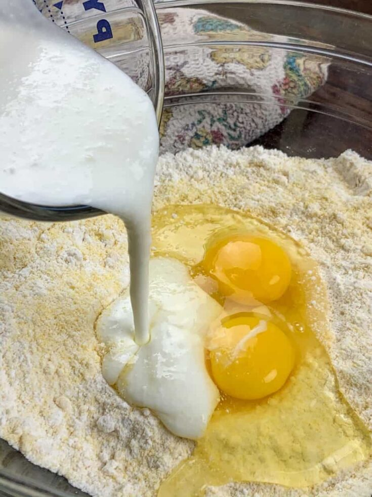 Pouring buttermilk into a glass bowl with cornbread mix and eggs