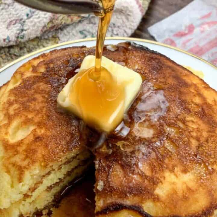 Pouring syrup over butter on Jiffy Cornbread Pancakes