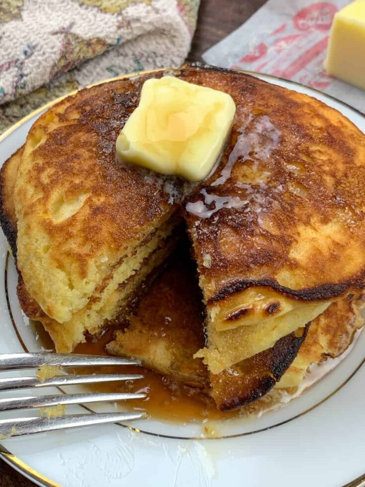Jiffy Cornbread Pancakes on a plate with butter on top