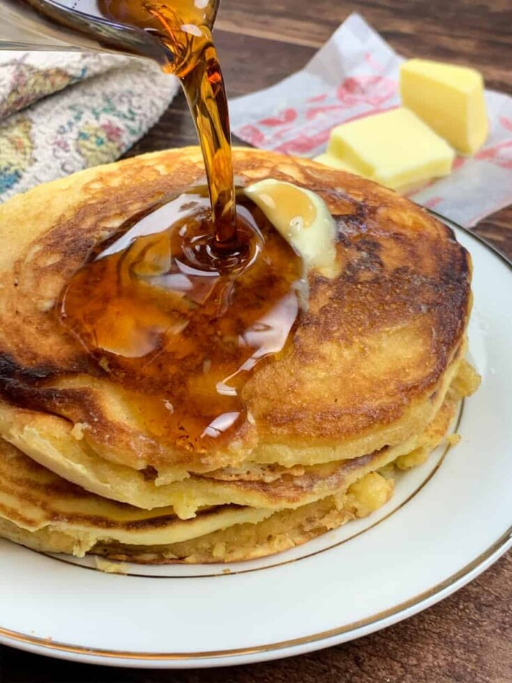 Pouring syrup over Jiffy Cornbread Pancakes