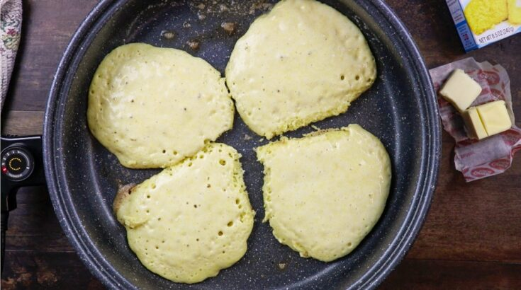 Four pancakes cooking in a skillet