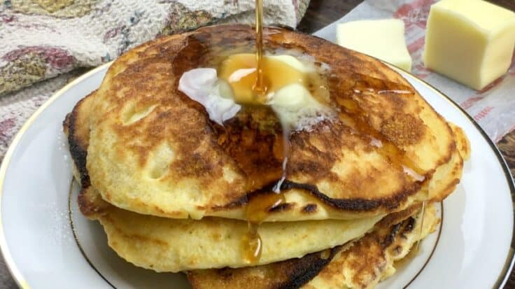 Four cornbread pancakes stacked on top of each other with butter and syrup on top