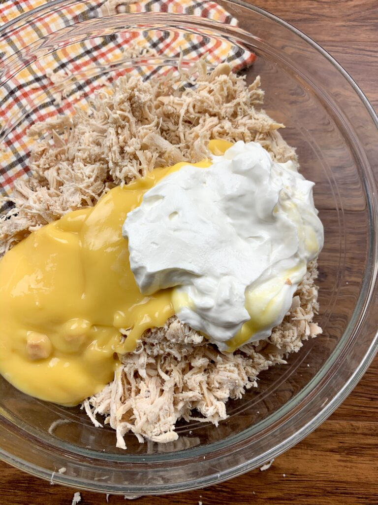 Shredded chicken, cream of chicken soup, and sour cream in a glass bowl