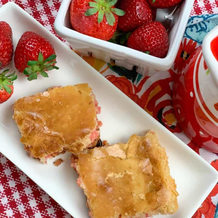 Two strawberry chess squares on a white plate