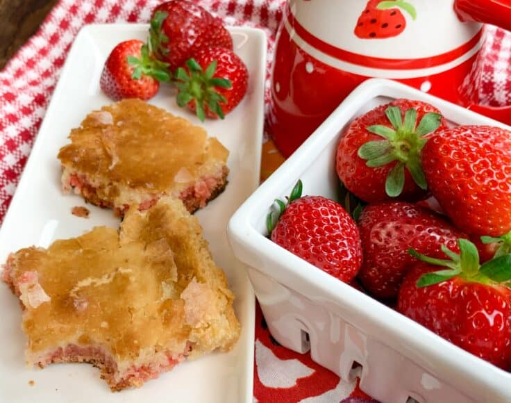 Strawberry chess squares on a white plate with strawberries in a bowl
