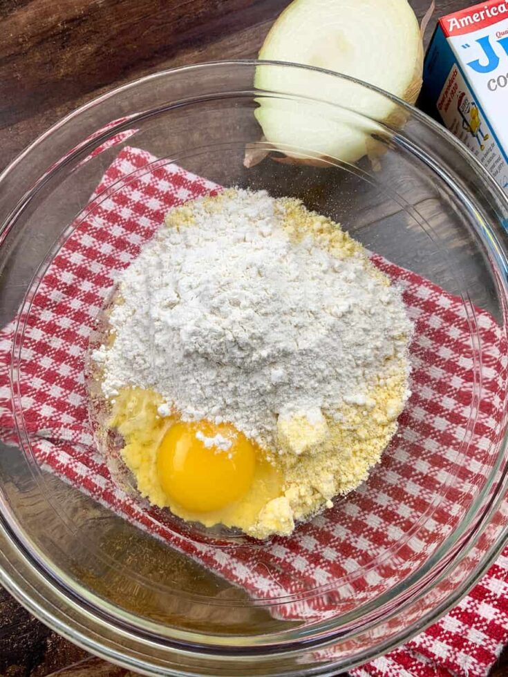 Corn muffin mix, an egg, and flour in a glass bowl.