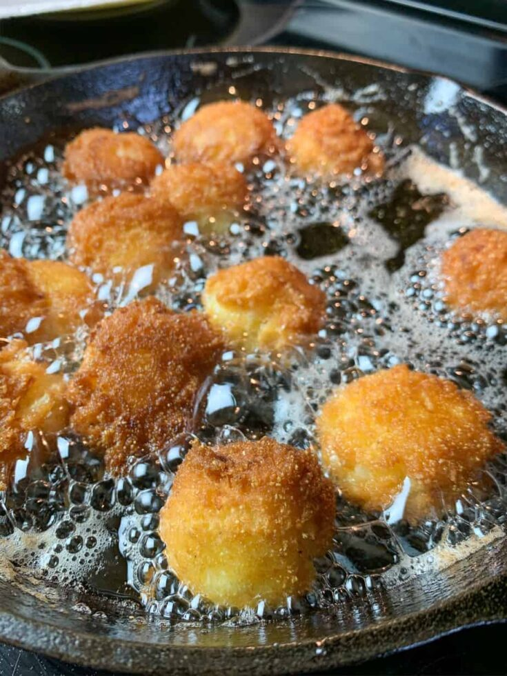 Hush puppies frying in a skillet with oil.