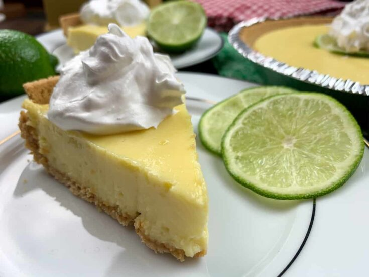 A slice of key lime pie on a plate with whipped topping.