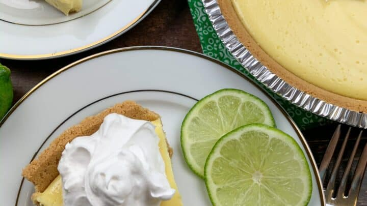 A slice of key lime pie in a plate with limes.