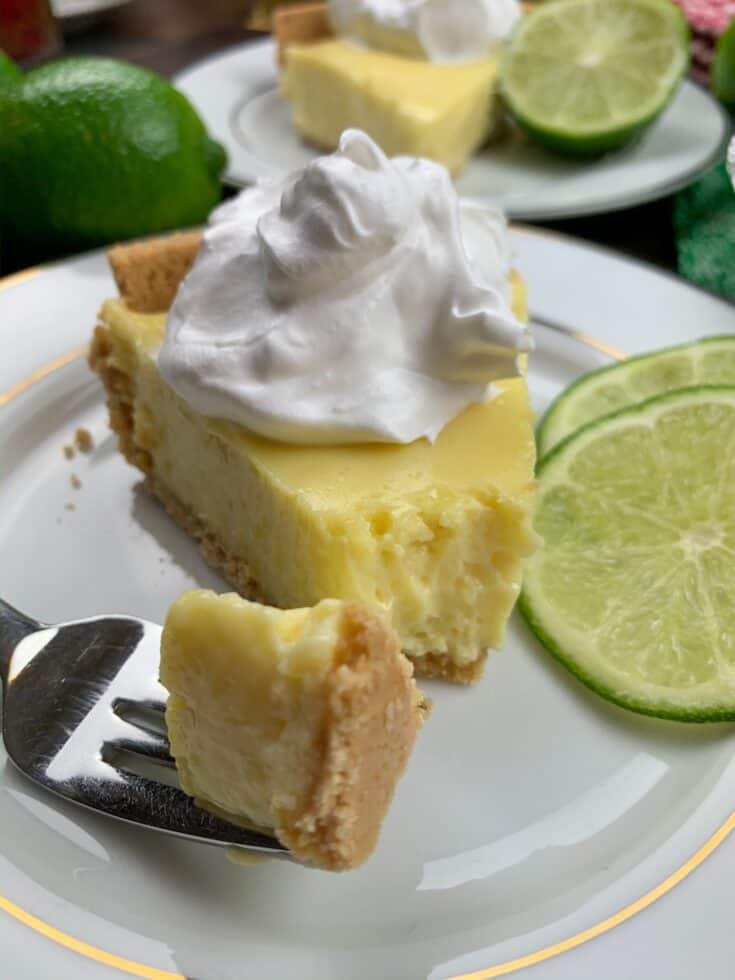 Key lime pie on a plate with slices of lime