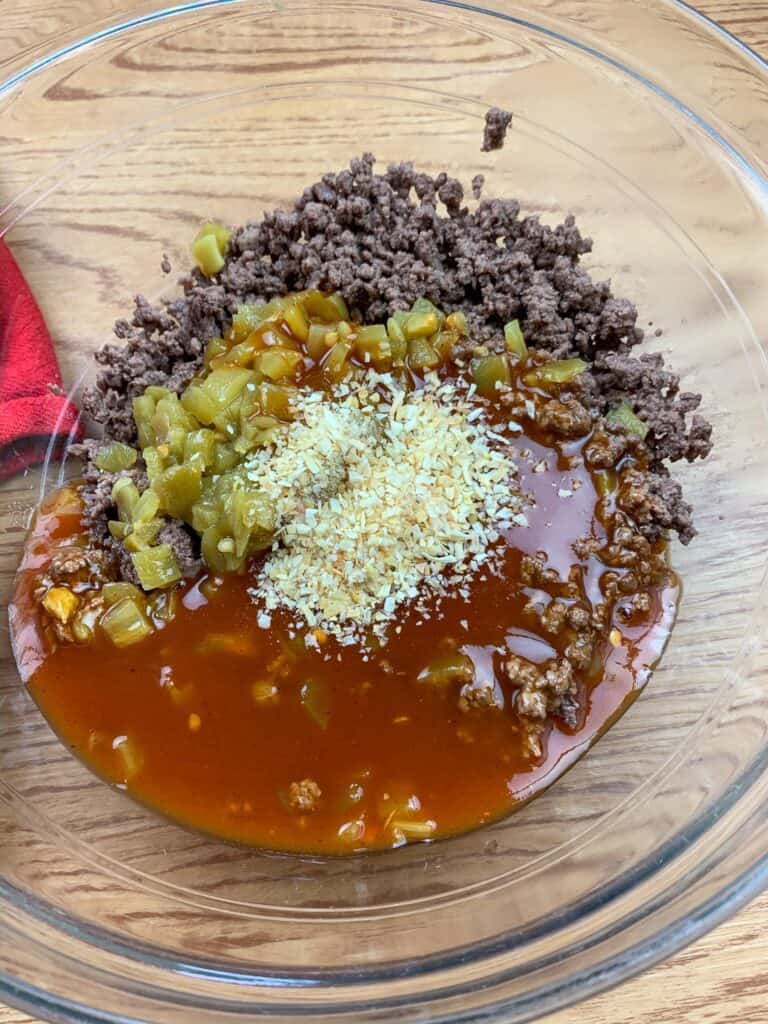 Ground beef, enchilada sauce, garlic, chiles, and minced onion in a large glass bowl.