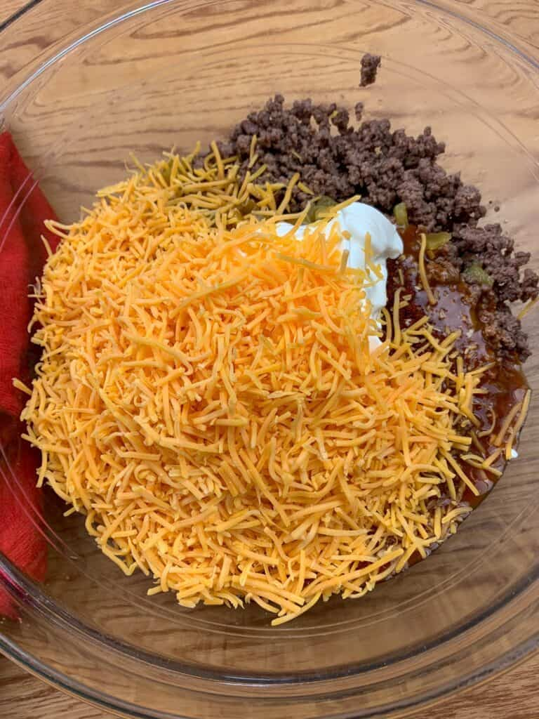Shredded cheddar cheese sitting on top of a bowl of tamale pie ingredients.