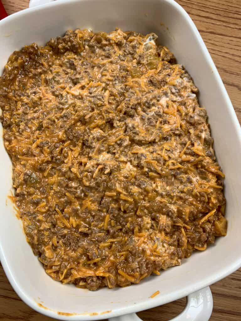 Adding ground beef tamale mixture to the bottom of a casserole dish