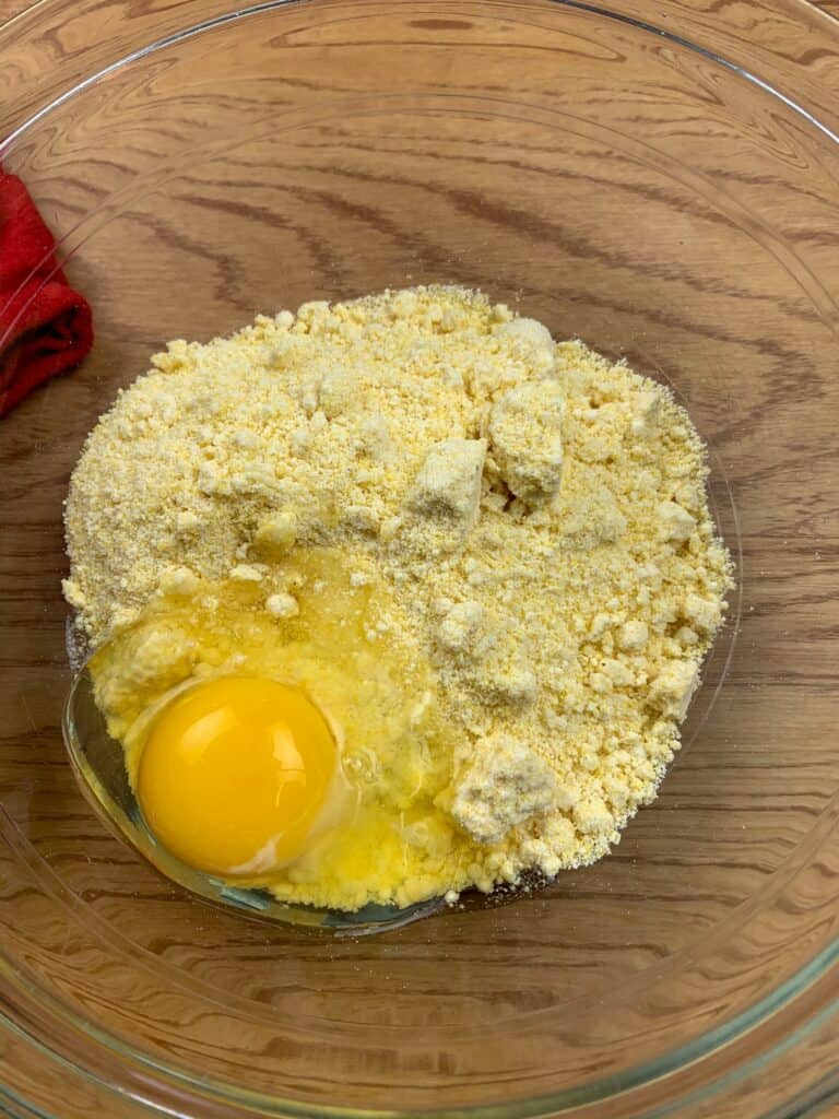 Jiffy Corn Muffin Mix and an egg in a glass bowl