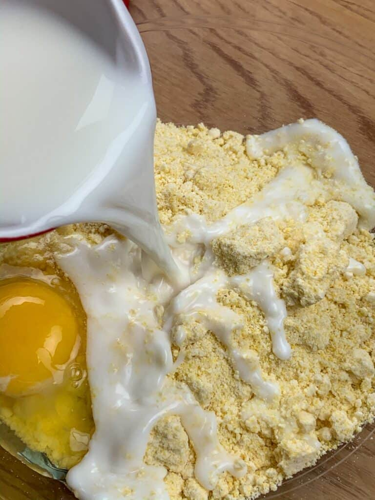 Pouring milk into a bowl with Jiffy Muffin Mix and egg.