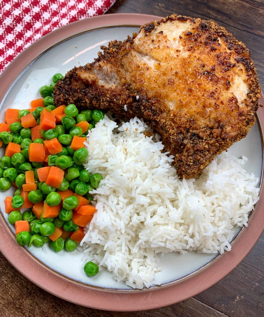 Rice, mixed vegetables, and a breaded pork chop on a white and brown plate.