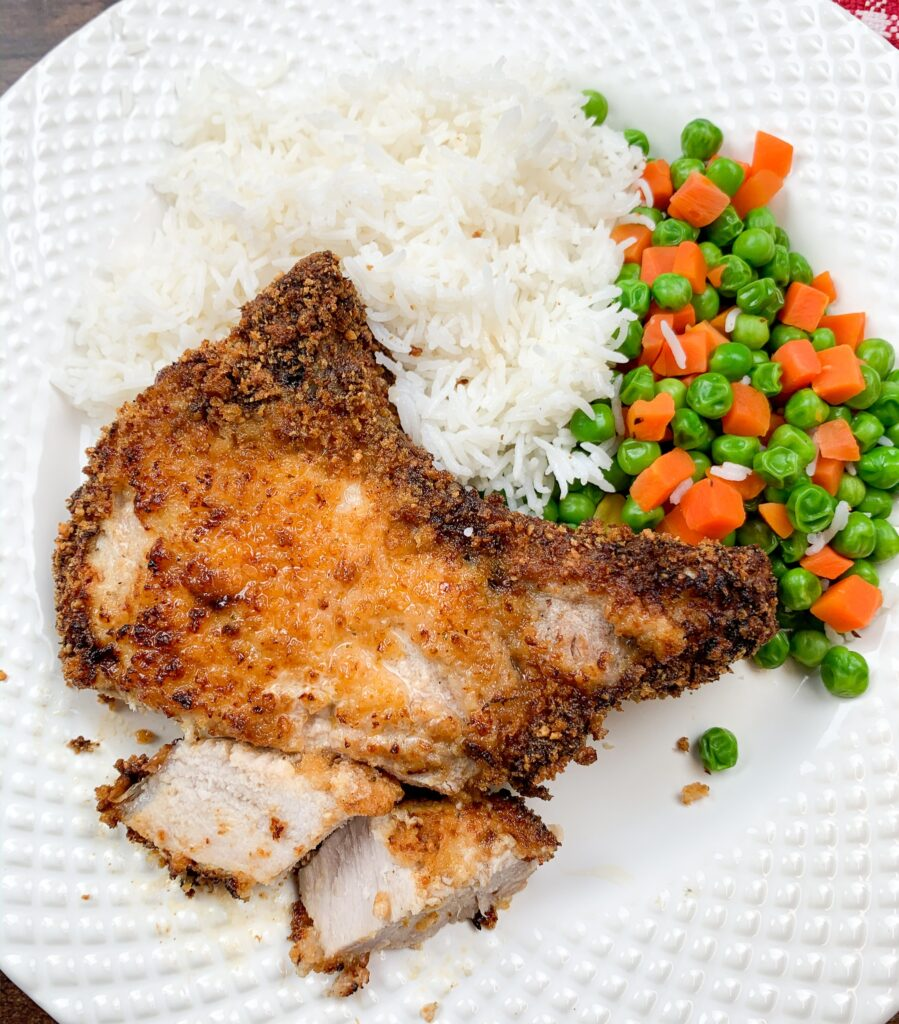 Breaded air fryer pork chops on a white plate with white rice and mixed veggies.
