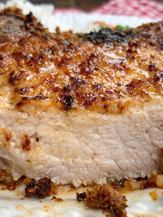 A pork chop, cooked in an air fryer, on a white plate.