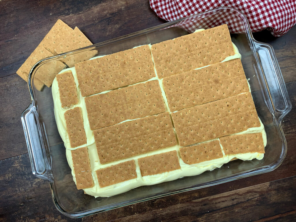 Graham crackers on top of pudding in a glass casserole dish