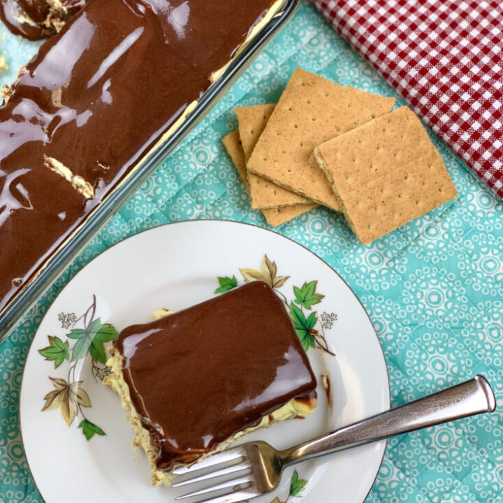 Eclair cake sitting on a white plate and blue placemat.