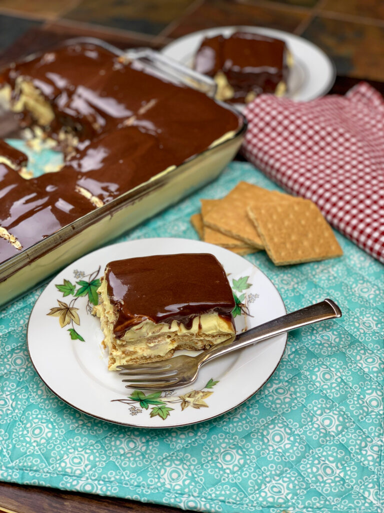 No bake eclair cake on a white plate and blue placemat
