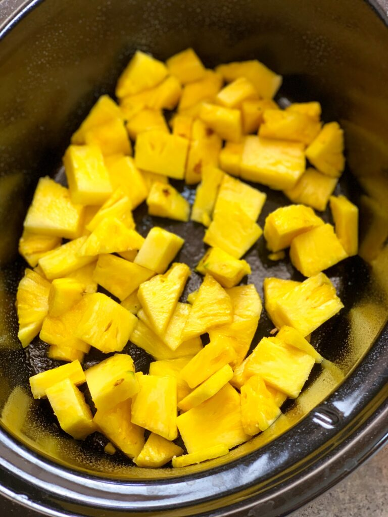 Cubes of pineapple in a black Crock Pot