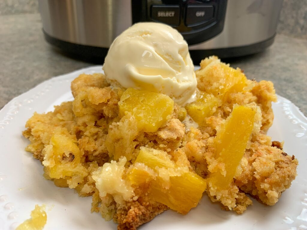 Pineapple dump cake, with a scoop of vanilla ice cream, on top.