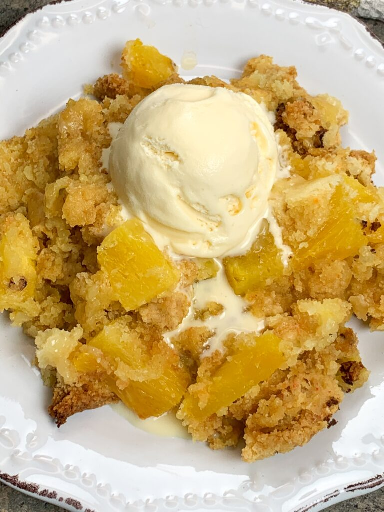 Pineapple dump cake on a plate with an ice cream scoop on top.