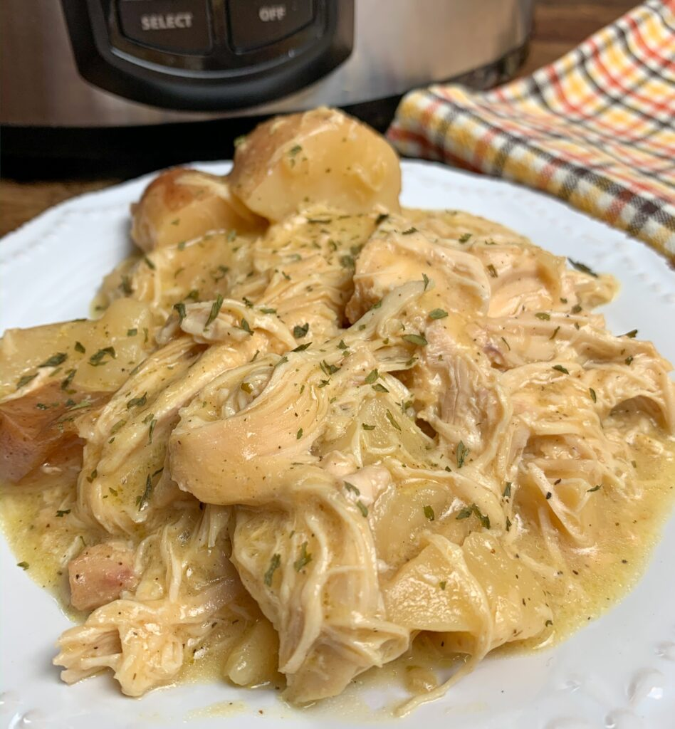 Slow Cooker Chicken and potatoes with creamy ranch gravy on a white plate.