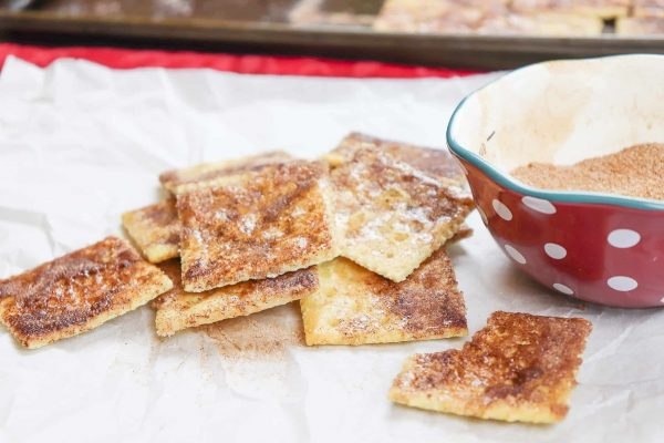 Cinnamon sugar crackers on parchment paper next to a bowl