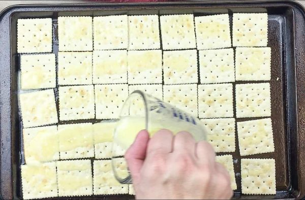 Pouring butter over crackers on a cookie sheet.
