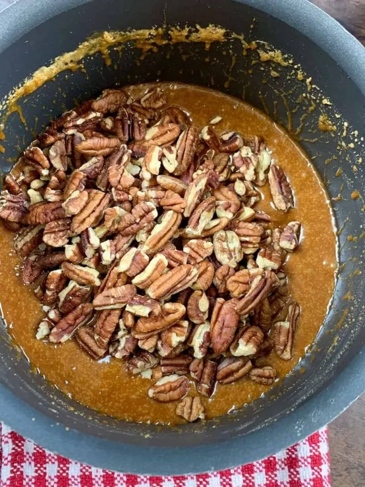 Pecans and boiling sugar in a saucepan.