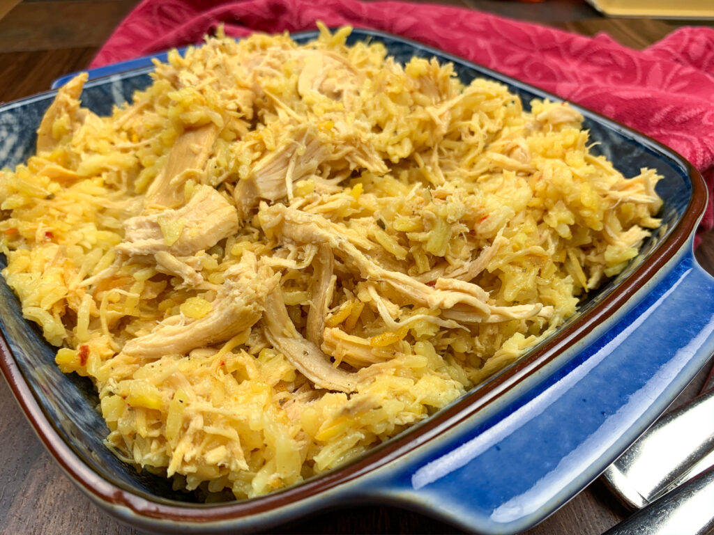 Slow cooker shredded chicken and Spanish rice in a large serving dish.