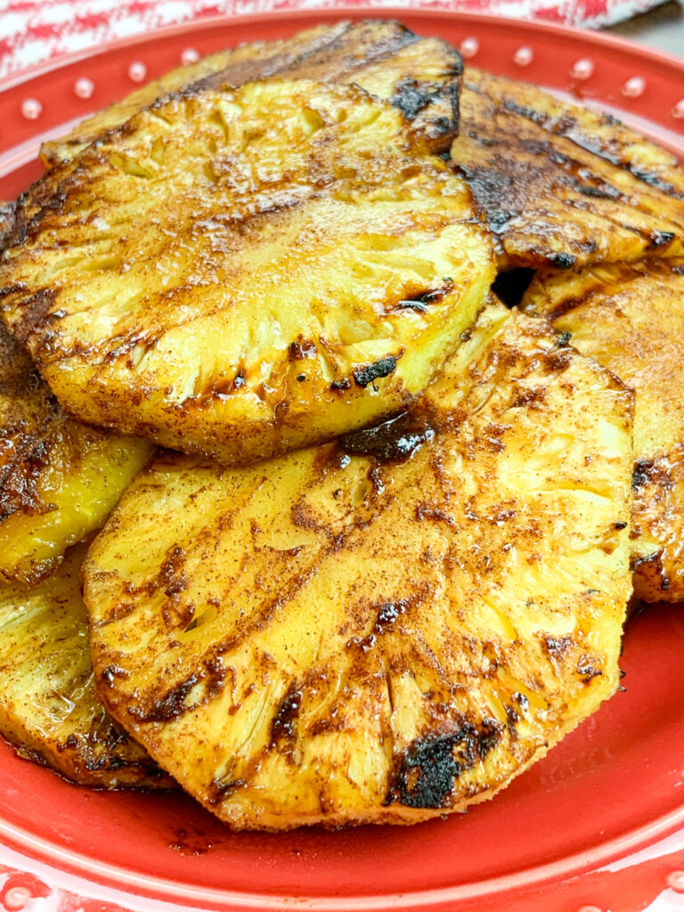 A red plate with slices of grilled pineapple.