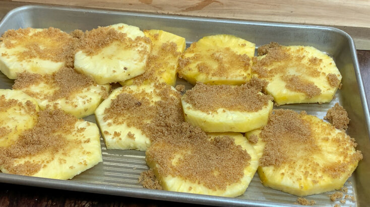 Sliced pineapple on a cookie sheet with brown sugar on top