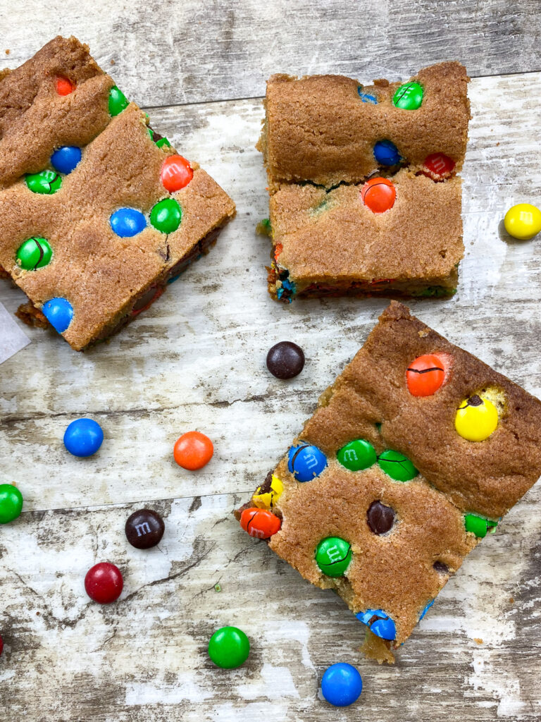 Cookie bars on a counter with M&Ms scattered.