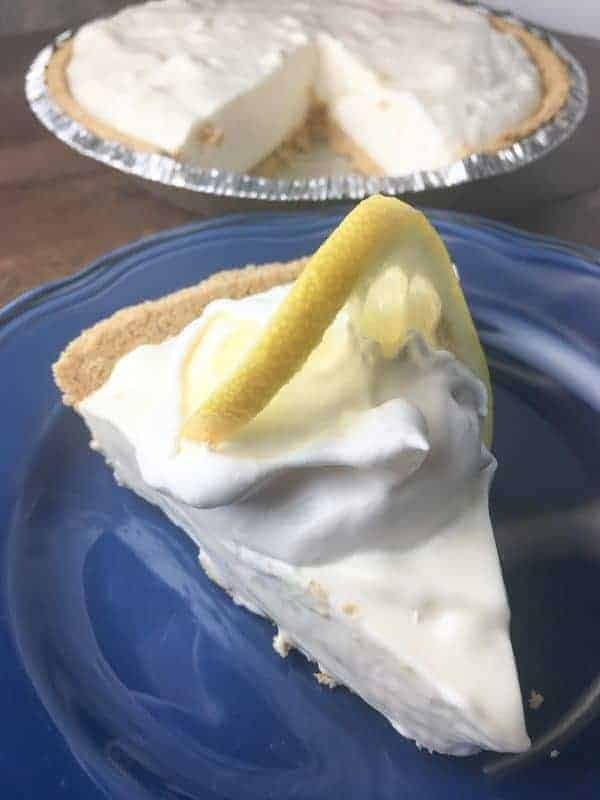 A slice of lemon cream pie on a blue plate.