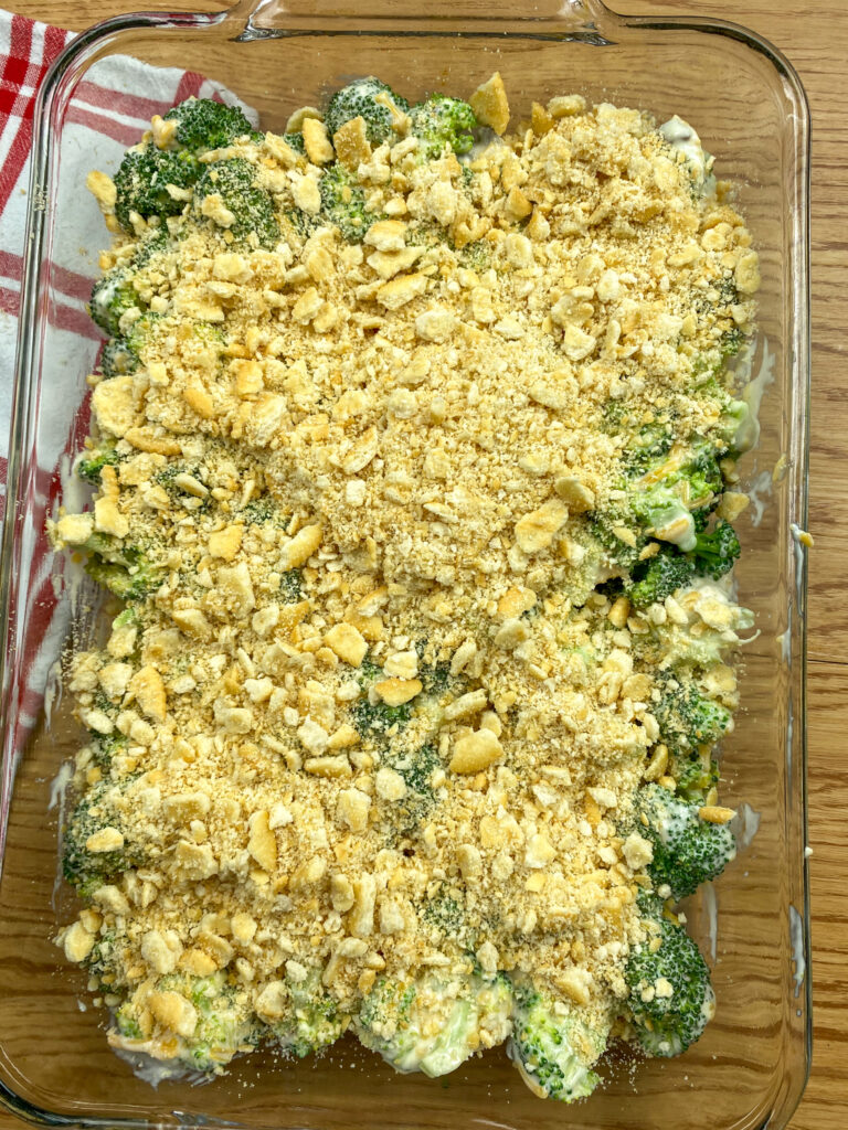 Broccoli cheese casserole with crushed Ritz Crackers in a baking dish.