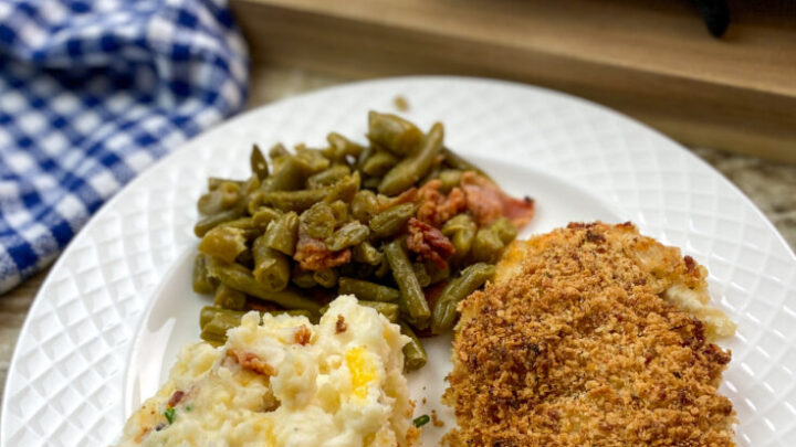 Panko chicken breast on a white plate with green beans and potatoes.