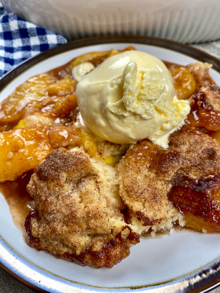 Peach cobbler on a plate topped with vanilla ice cream.