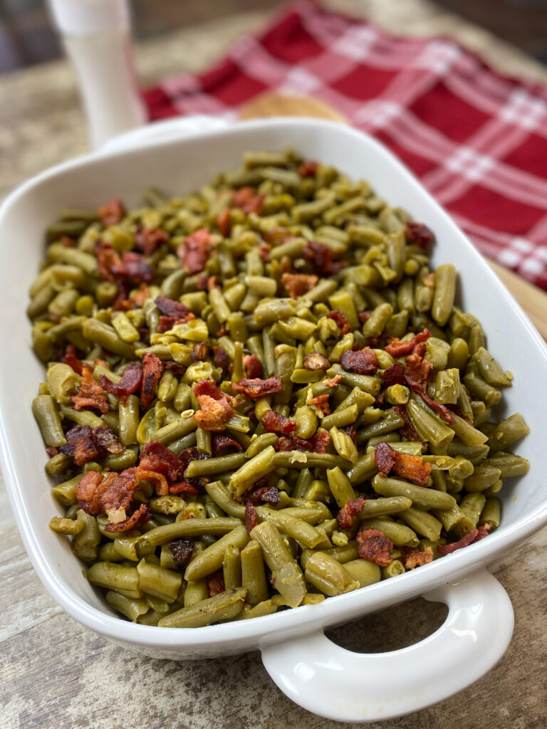 Green beans and bacon in a dish on the counter.