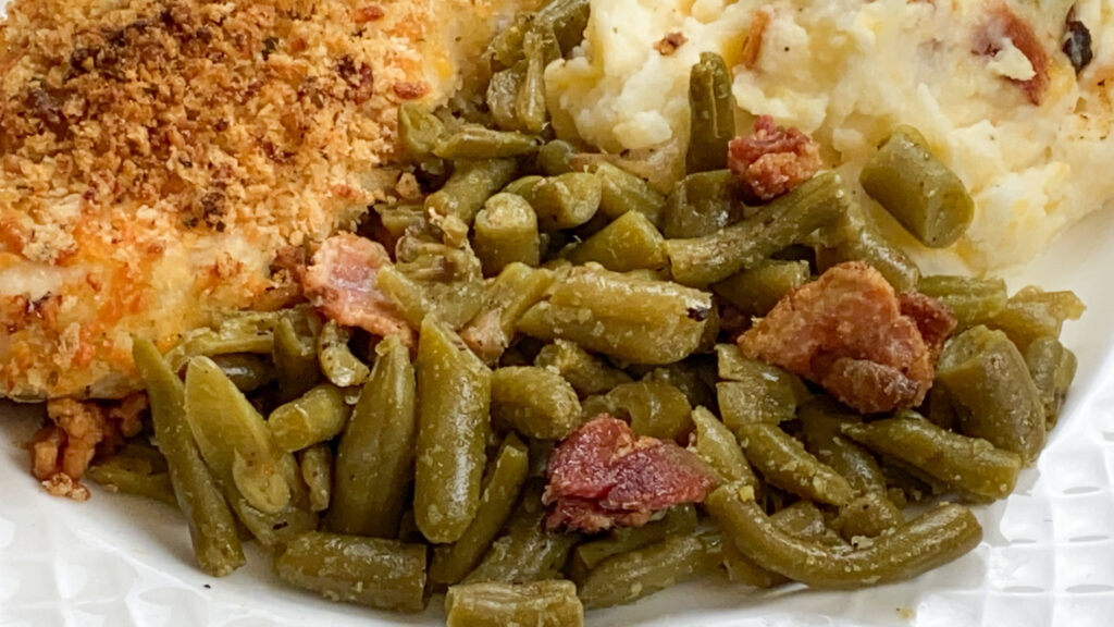Green beans on a plate with bacon.