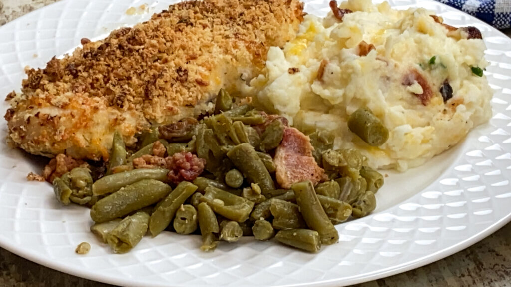 Green beans with chicken and mashed potatoes on a plate.